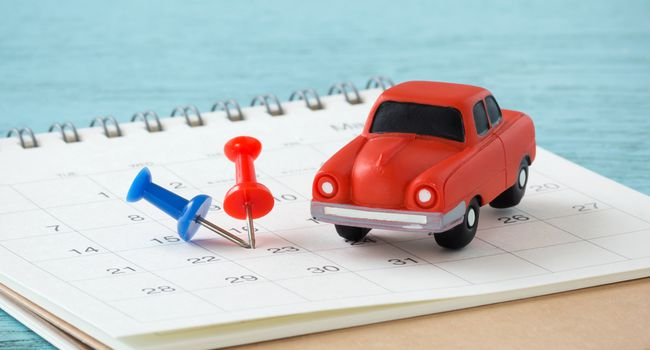 Toy car and pins on calendar