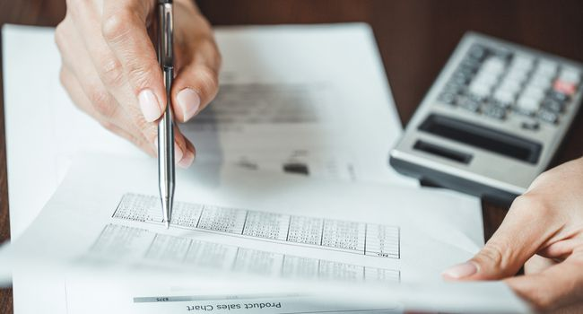 Close up of businesswomans hand with pen doing some financial calculations