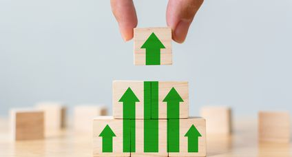 Ladder career path for business growth success process concept. Wood block stacking as step stair with arrow up. Hand putting wooden cube block on top pyramid