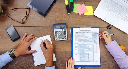 Teamwork in office – man and woman dealing with financial data, taxation and stock markets