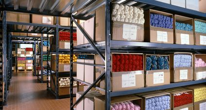 Balls of wool arranged on shelves in a textile warehouse