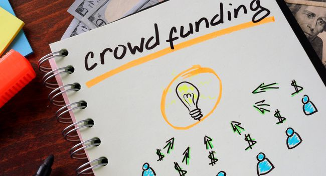 Notebook with crowd funding sign on a table.