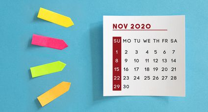 Calendar concept. November 2020 Calendar On The White note paper. Colored arrow-shaped sticky notes point to it.