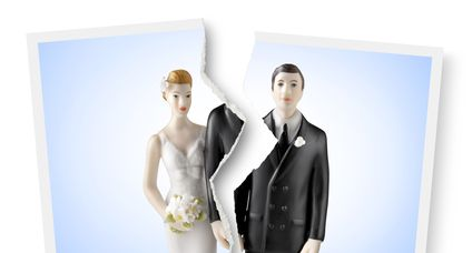 Divorce. Torn photograph of wedding cake topper.