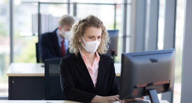 Business woman with curly blonde hair wearing a mask sitting in office