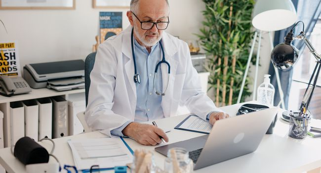 Male doctor counseling, helping patient online, medic using laptop for video call