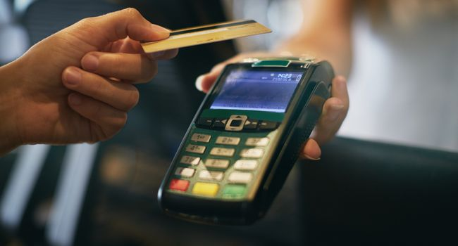 Hand offering credit card to hand-held point-of-sale device