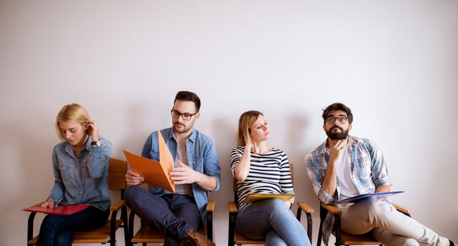Group of upset and bored young people sitting in a row in the waiting room with a folder in hand before an interview with the entrepreneur.