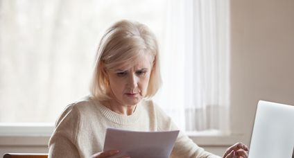 Serious frustrated middle aged woman troubled with domestic bills