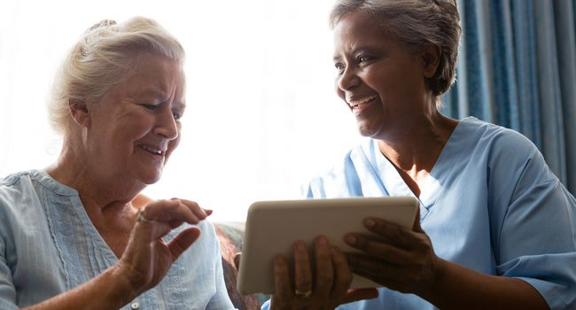 Cheerful senior woman with doctor using digital tablet while sitting on sofa