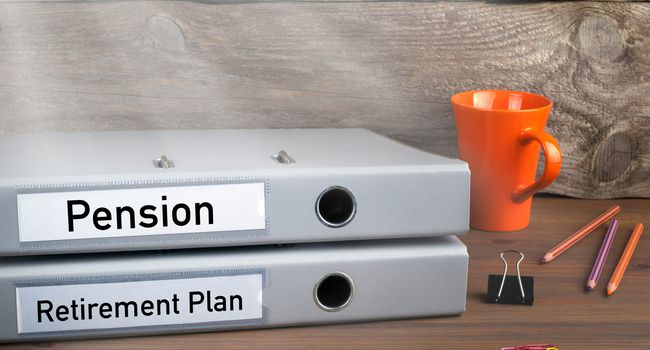 Retirement Plan and Pension – two folders on wooden office desk
