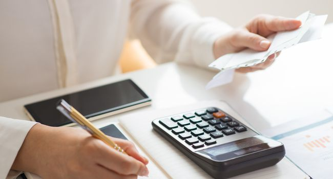 Closeup of person holding bills and calculating them
