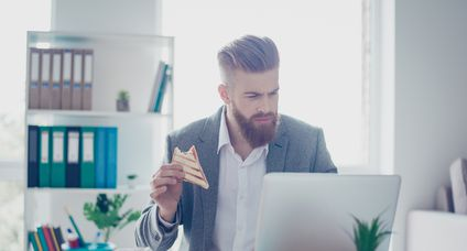 Young bearded businessman is having a sandwich while reading his emails on laptop in office