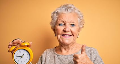 Senior beautiful woman holding alarm clock standing over isolated yellow background happy with big smile doing ok sign, thumb up with fingers, excellent sign