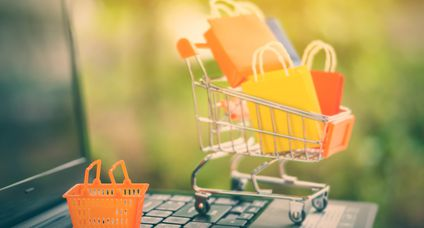 Online shopping and ecommerce via internet concept : Mini orange basket on a laptop computer keyboard with paper shopping bags in a shopping cart behind. Consumer always buy things from online stores.