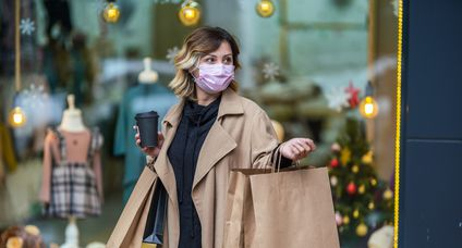 Young Woman holding shopping bags and wearing face mask because of Covid-19