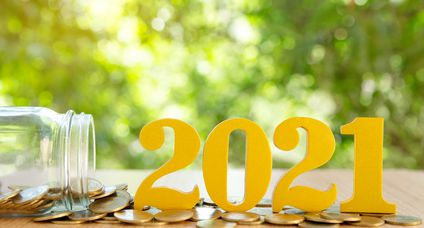 Word 2021 put on coins and glass bottles with coins inside on green bokeh background.Savings New year Concept.
