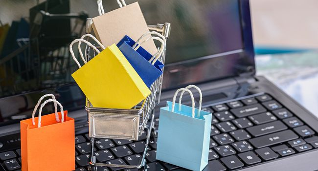 Five paper shopping bags and a shopping cart on a laptop keyboard.