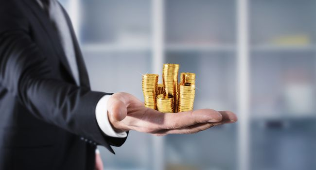 Businessman hold piles of money. Concept of success and company growth