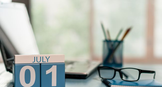 July 1st. Day of the month 1 , wooden color calendar on business workplace background. Summer concept. Empty space for text