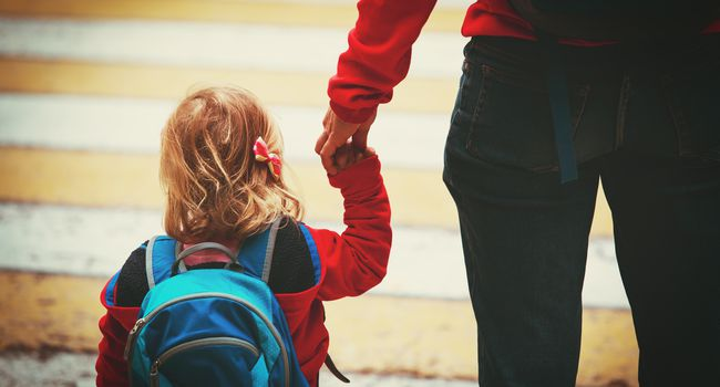 parent walking little daughter to daycare