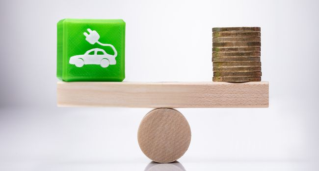 Eco Car Icon Cubic Block And Coins Balancing On Seesaw