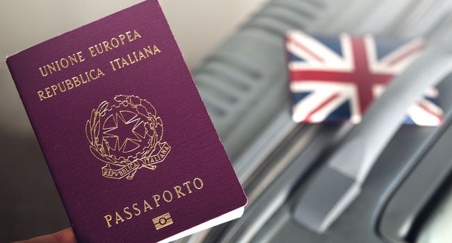An italian passport holded over a suitcase with an english id holder on it