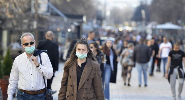 Man and woman walking in the the city center wearing protective masks