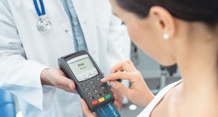 Doctor is holding payment terminal in hands