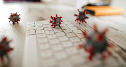 Model of corona virus on desk and keyboard in office