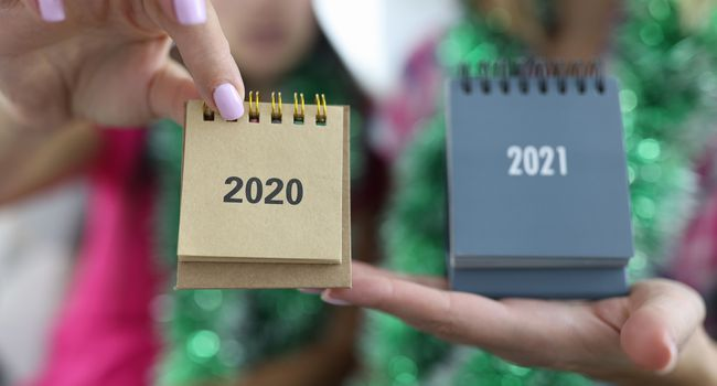 Female hands holding calendars 2020 and 2021 closeup