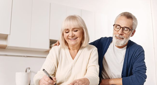 Harmonious aged couple signing documents at home